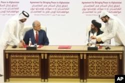 FILE - US peace envoy Zalmay Khalilzad, left, and Mullah Abdul Ghani Baradar, the Taliban group's top political leader, sign a peace agreement between Taliban and US officials in Doha, Qatar, Feb. 29, 2020.