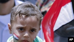 A woman carries a child during a demonstration in Tahrir Square in Cairo May 20, 2011