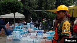 A soldier stands guard next to donations of bottled water for rescue workers and victims next to a collapsed building after earthquake in Mexico City, Mexico, Sept. 20, 2017.