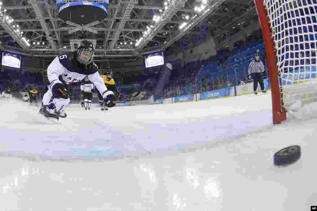 Kanae Aoki of Japan races after the goal shot by Franziska Busch of Germany during the closing seconds of the women's ice hockey game at the 2014 Winter Olympics, Feb. 13, 2014.