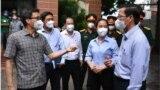 Bà Hờ Rin (nữ, áo xanh), báo cáo tình hình chống dịch tại Quận 6. Phó thủ tướng Vũ Đức Đam đứng bìa trái. (Hình: Thuận Thắng/zingnews.vn)