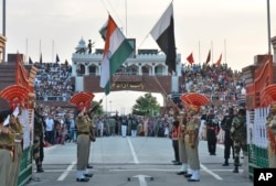 FILE- Indian and Pakistani flags are lowered during a daily retreat ceremony at the India-Pakistan joint border check post of Attari-Wagah near Amritsar, India, July 21, 2015.