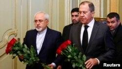 20일 러시아 모스크바에서 회동한 세르게이 라브로프 러시아 외무장관(오른쪽)과 모하마드 자바드 자리프 이란 외무장관이 암살당한 러시아 대사를 추모하는 화환을 들고 있다.