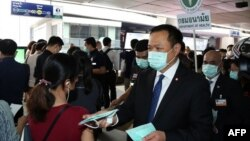泰国公共卫生部长阿努丁在曼谷的一个高架轻轨车站发放疫情防护口罩。(2020年2月7日)