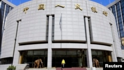 FILE - A woman walks out of the headquarters of the People's Bank of China (PBOC), the central bank, in Beijing.