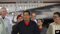 Venezuela's President Hugo Chavez (C) gestures after his arrival from Cuba, at Simon Bolivar International Airport in Caracas, July 23, 2011 (this image has been supplied to Reuters by a third party)