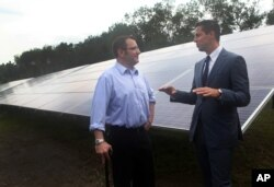 Michael Maravelias, left, an NRG Home Solar customer, and Kelcy Pegler Jr., president of NRG Home Solar, right, talk in front of solar panels from the NRG shared solar facility in Freetown, Massachusetts, July 27, 2015.