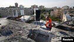 Seorang anggota Tim SAR tengah memeriksa sebuah atap bangunan yang hancur akibat serangan roket di kota Ashkelon, Israel (Foto: dok). Polisi Israel mengatakan telah menemukan sisa-sisa roket dekat kota Ashkelon, di selatan Israel, Selasa (26/2).