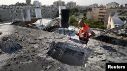 Một nhân viên cứu nạn Israel nhìn căn nhà bị hư hại vì rocket