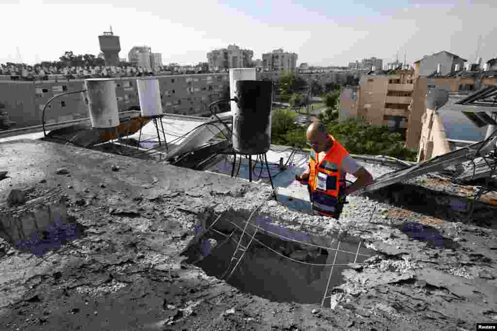 An Israeli rescue worker looks at the roof of a building damaged by a rocket in the coastal city of Ashkelon, November 18, 2012. (Reuters)