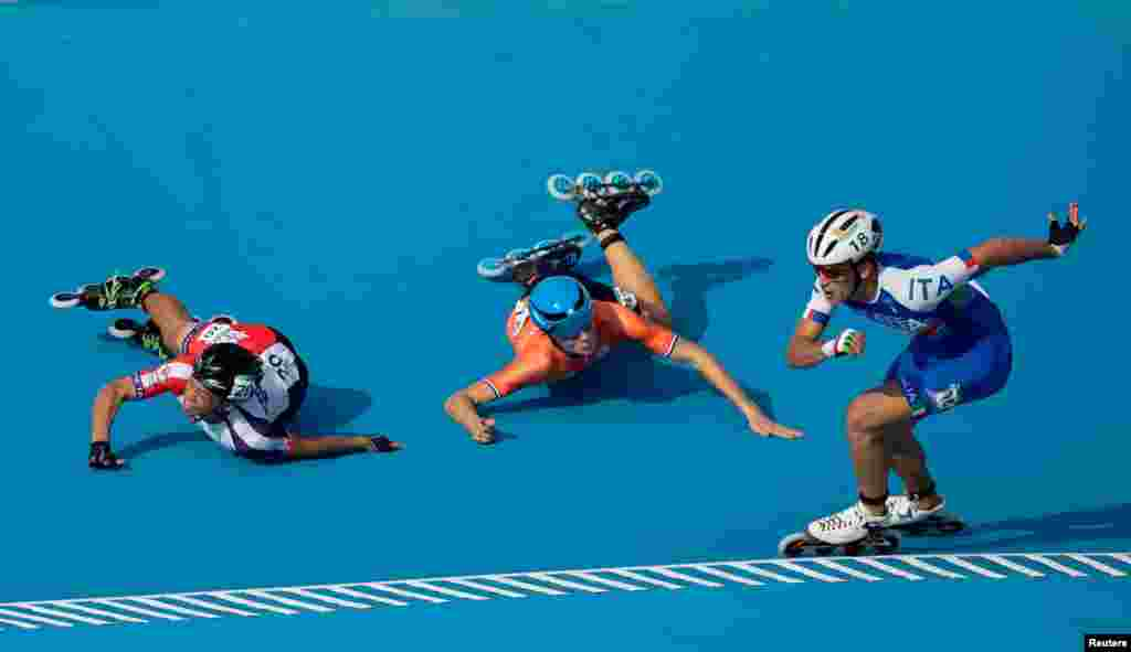 Vincenzo Maiorca of Italy takes the lead as Chiawei Chang of Taiwan and Merijn Scheperkamp of the Netherlands fall during the Roller Speed Skating Mens Combined Speed Event Final at the Paseo De La Costa during the Youth Olympic Games, Buenos Aires, Argentina, Oct. 8, 2018.