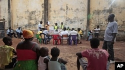 Local residents watch as ballots are counted at an outdoor polling station in Bissau, Guinea-Bissau, March 18, 2012.