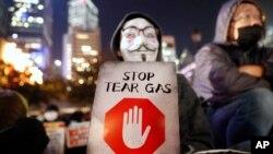 一名香港示威者手举标语牌抗议港警使用催泪弹。(2019年12月6日)
