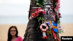Женщина смотрит на дерево, декорированное цветами и фотографиями в память жертв цунами 2004 года. Таиланд. 26 декабря 2014 г.