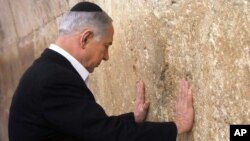 Israeli Prime Minister Benjamin Netanyahu prays at the Western Wall in Jerusalem's Old City, Feb. 28, 2015.