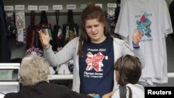 A member of staff talks to customers at a London 2012 shop selling official merchandise in Green Park, central London, July 21, 2012.