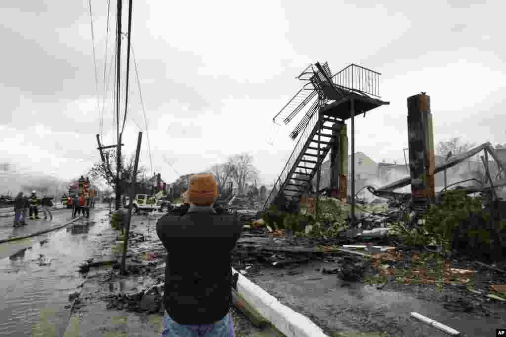 A man photographs damage caused by a fire fire in the Belle Harbor neighborhood in the New York City borough of Queens Oct. 30, 2012, in New York.
