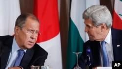 Menteri Luar Negeri Rusia Sergei Lavrov (kiri) dan mitranya dari AS John Kerry berbincang dalam pertemuan mengenai Suriah di New York (22/9). (AP/Jason DeCrow)
