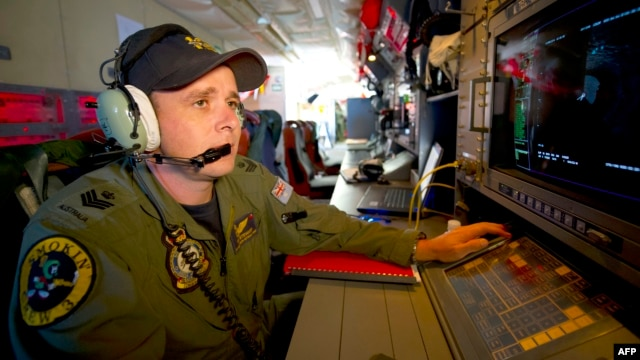 Royal Australian Air Force Airborne Electronics Analyst Flight Sergeant Tom Stewart from 10 Squadron watching a radar screen for signs of debris on board an AP-3C Orion over the Southern Indian Ocean during the search for missing Malaysian Airlines flight