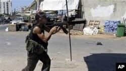 Seorang warga Suni melancarkan tembakan dalam bentrokan sektarian di Tripoli, Lebanon utara (24/8).