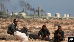 FILE - Anti-Gadhafi rebels sit on the ground near an oil facility in Ras Lanuf, Libya. The struggle for the Ras Lanuf refinery and nearby Sidr depot threatens to spiral into an all-out conflict between east and west.