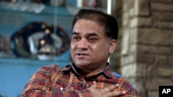 FILE - Ilham Tohti, an outspoken scholar of China's Turkic Uighur ethnic minority, speaks during an interview at his home in Beijing, China.