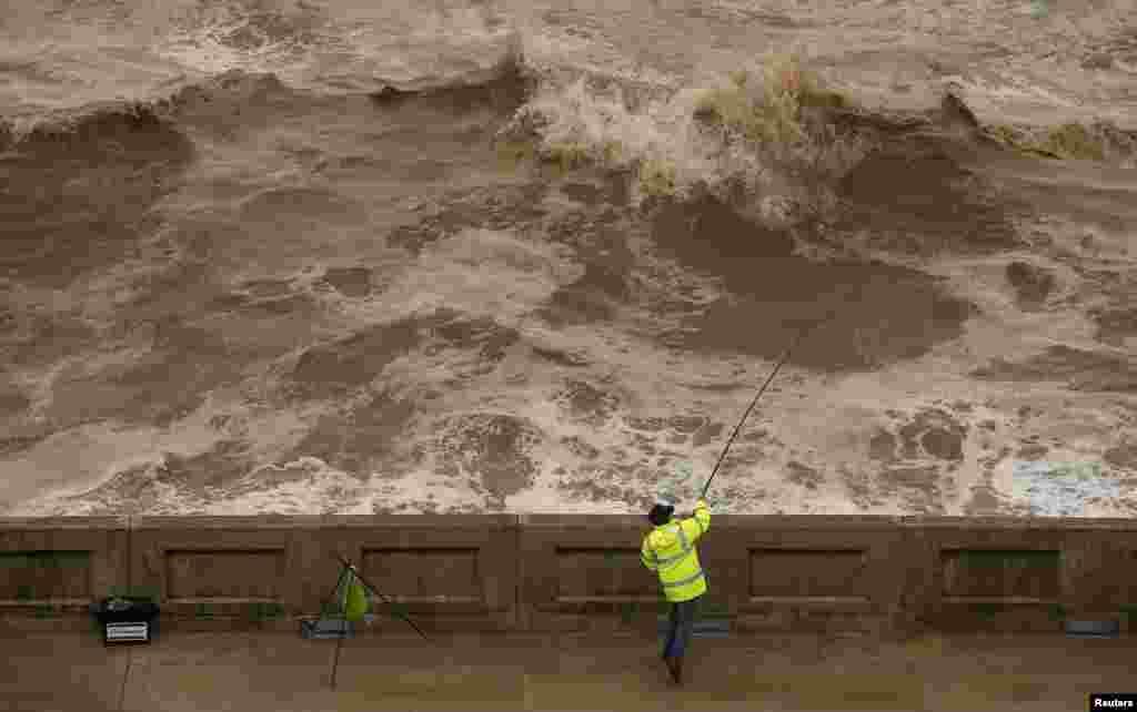 A fisherman casts his line into heavy seas off the promenade in Blackpool, Britain.