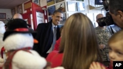 President Barack Obama visits patrons at We B Smokin' bar-b-que on the outskirts of Osawatomie, Kansas, Tuesday, Dec. 6, 2011.