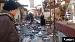 A man looks at the site of bomb attack at a marketplace in Baghdad's Doura District, Iraq, Dec. 25 2013.