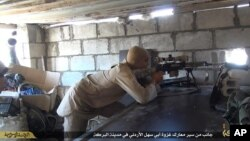 FILE - This file picture released on July 13, 2015 by the Rased News Network, a Facebook page affiliated with Islamic State militants, shows an Islamic State militant sniper in position during a battle against Syrian government forces, in Deir el-Zour province, Syria.