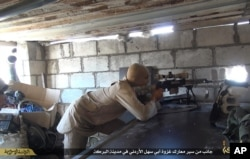 FILE - This file picture released on July 13, 2015 by the Rased News Network, a Facebook page affiliated with Islamic State militants, shows an Islamic State militant sniper in position during a battle against Syrian government forces, in Deir el-Zour pro