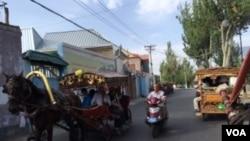 伊犁喀赞其民俗区马车摩托车并行不悖。