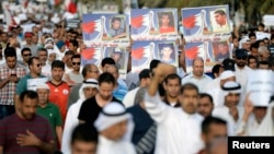 Protesters hold banners as they shout anti-government slogans during a protest in Budaiya west of Manama, April 4, 2014.