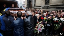 People carry the coffin of Bogdan Solchunuk, in front of the St. Paul and Peter church, during his funeral, in Lviv, western Ukraine, Feb. 22, 2014.
