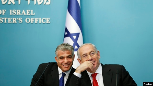 FILE - Israeli Prime Minister Benjamin Netanyahu (R) and Finance Minister Yair Lapid smile during a joint news conference in Jerusalem, July 2013.