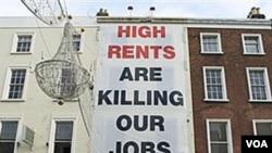 Este cartel en Dublín, Irlanda, critica como el alto costo de la vivienda está afectando los trabajos.