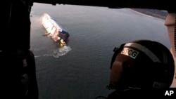 8일 미국 조지아주 브런즈윅항 외곽 해상에서 전도돼 옆으로 기운 현대글로비스 소속 자동차 운반선 골든레이호가 헬기 문 사이로 보인다.