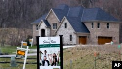FILE - Real estate signs mark the lots near one of the new homes for sale in a development for new homes in Cranberry Township, Butler County, Pennslyvania, Feb. 27, 2017.