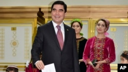 Turkmenistan President Gurbanguly Berdimuhamedov, center, smiles as he casts his ballot at a polling station in Ashgabat, Turkmenistan, Sunday, Feb. 12, 2017. (AP Photo, Alexander Vershinin)