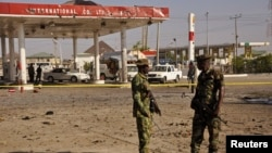 Members of the military stand at the scene of an explosion near a petrol station in Kano, Nigeria, Nov. 15, 2014.