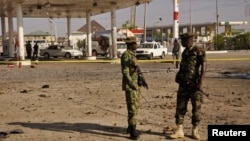 FILE - Members of the military stand at the scene of an explosion near a gas station in Kano, Nigeria, Nov. 15, 2014.