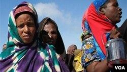 Wanita dan anak-anak mengantri untuk menerima bantuan makanan yang dibagikan di Mogadishu.