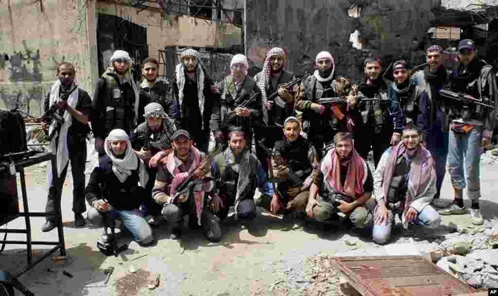 Para pejuang yang bergabung dalam Tentara Pembebasan Suriah berfoto bersama sebelum meninggalkan kota Homs, Suriah, 7 Mei 2014. (AP Photo/Komite Koordinasi Wilayah Khalidiya di Homs)