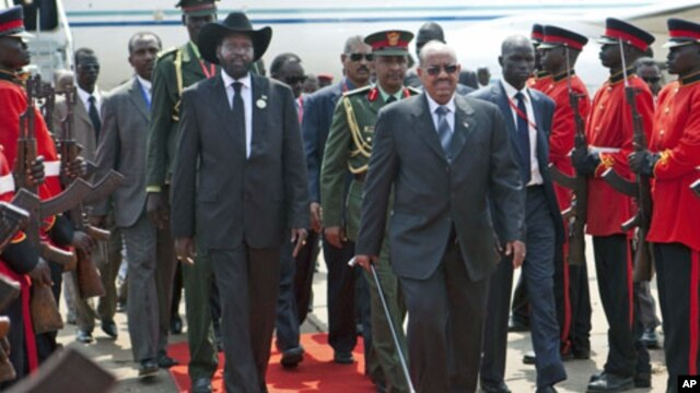 South Sudan's President Salva Kiir (L) and Sudan's President Omar Hassan al-Bashir walk at Juba airport,  July 9, 2011