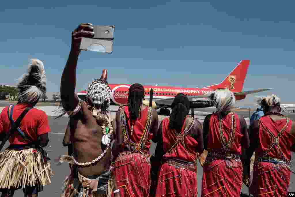 A dancer takes a selfie upon the arrival of the special aircraft carrying the FIFA World Cup Trophy during its World Tour at the Jomo Kenyatta International airport in Nairobi, Kenya.