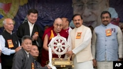 Tibetan spiritual leader the Dalai Lama presents a memento to Junior Indian Culture Minister Mahesh Sharma, second right, as he arrives to attend an event marking the beginning of the 60th year of the Dalai Lama's exile in India, in Dharmsala, India, Marc