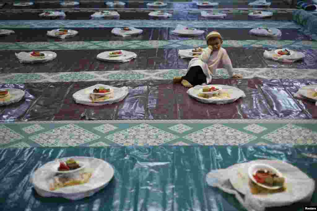 A boy watches helpers distribute food as he waits to break fast with devotees on the first day of Ramadan at a mosque in Singapore.