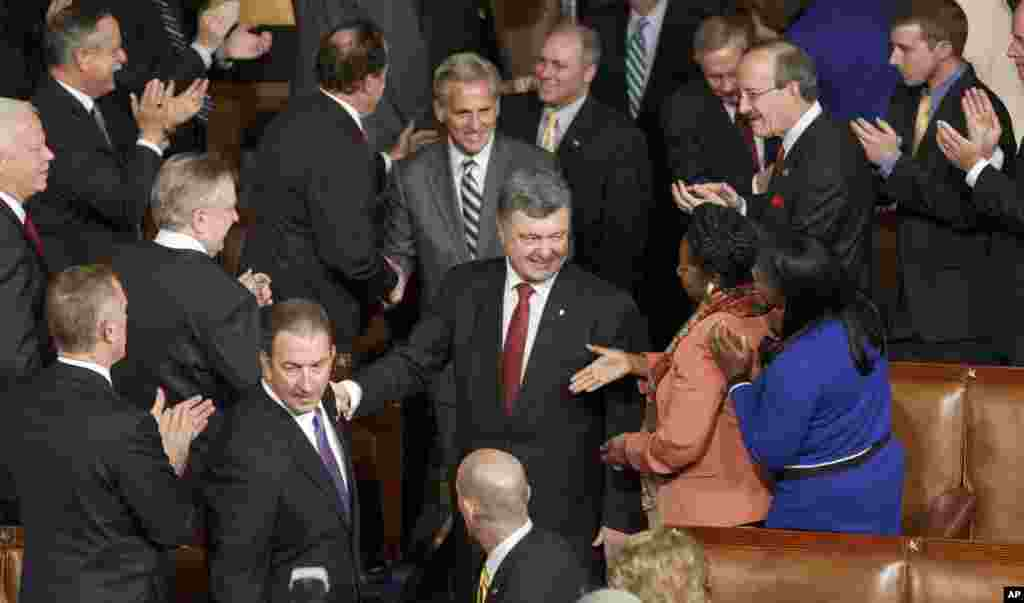 President Petro Poroshenko, escorted by House Majority Leader Kevin McCarthy, R-Calif., is welcomed by U.S. lawmakers as he arrives to address a joint meeting of Congress, at the Capitol in Washington, Sept. 18, 2014.