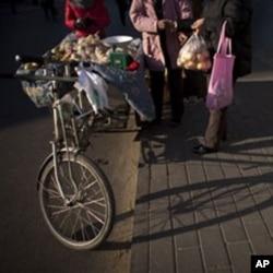 北京人向骑车的小贩买苹果