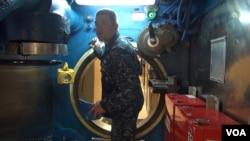A sailor navigates the narrow passageways of the USS Alaska, one of the Navy's Ohio-class submarines.(C. Babb/VOA)